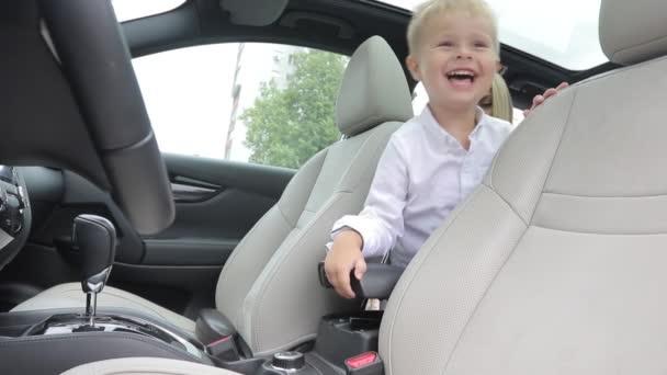 das Kind sitzt im Salon des Autos auf dem Rücken sitzend. tuschelt, spielt, will nicht im Kindersitz sitzen