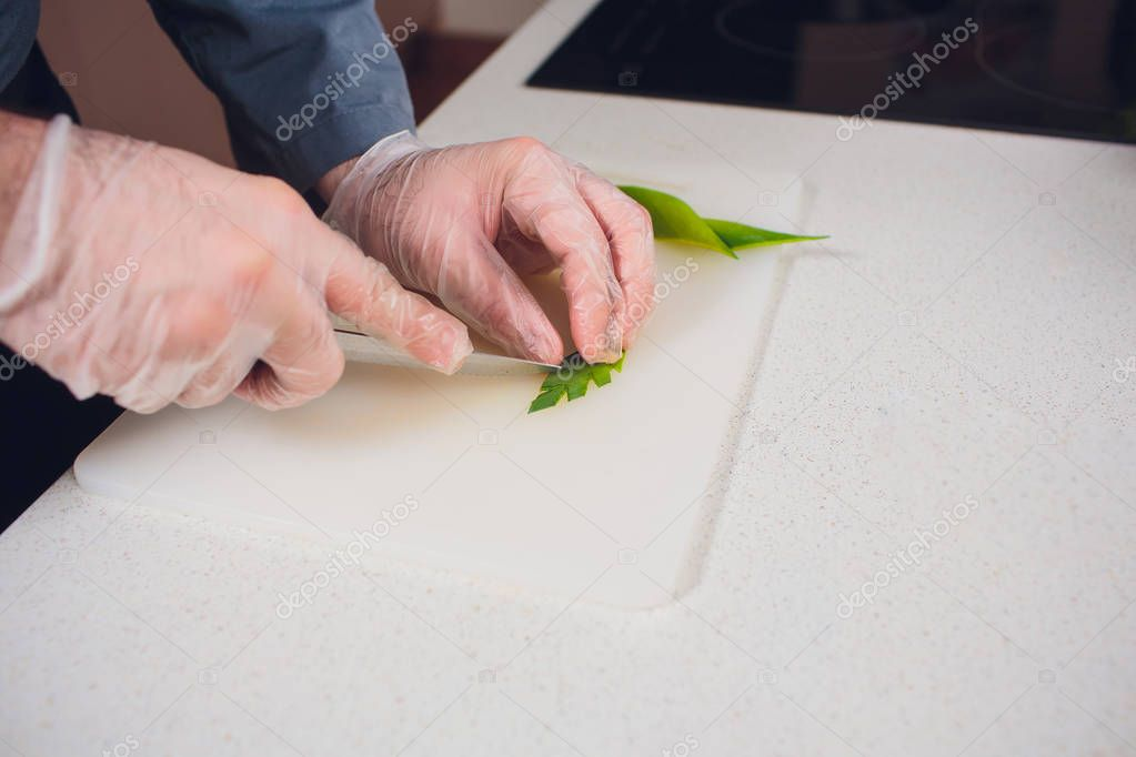 Housewife cutting celery cook in kitchen. Hands Slicing celery with Knife on chopping wooden board background. Cooking in kitchen concept.