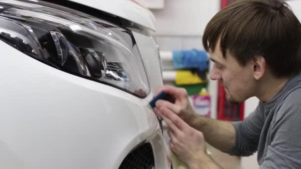 Lövés a kezét, az ember, aki szétválaszt a film a fehér motorburkolat drága autó közelről. Ez a film a jármű megvédi a durva festmény.