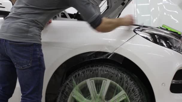 Zblízka střílel z rukou člověka, kteří odlepení fólie s bílým krytem drahé auto. Tento film chrání vozidlo před hrubý obraz.