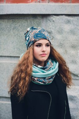 Portrait of funny young girl in the autumn weather in warm clothes and hat.
