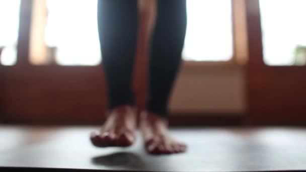 Krásná mladá žena nosí bílé sportovní set a smartwatch cvičit proti šedé zdi, dělá jógu nebo pilates cvičení. Směrem nahoru Pes póza, Urdhva mukha shvanasana. Celé délce. Příprava