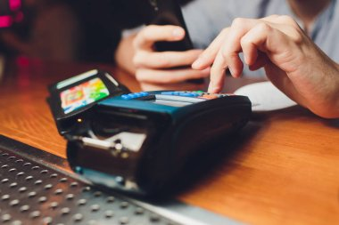 Woman hand with credit card swipe through terminal for sale in restaurant.
