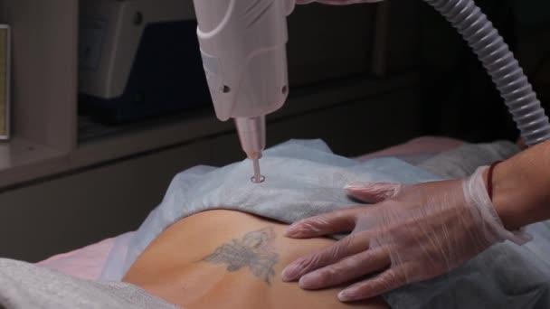 Cosmetologo con paziente e professionale tatuaggio rimozione laser nel salone.