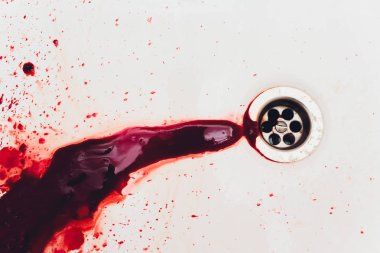 Blood draining from white bathroom basin. Bloody stains in the waterbasin hole. Sink run with blood floods. Red paint dripples to the washbowl drain. Accident with human injury. Bleeding in bathroom.
