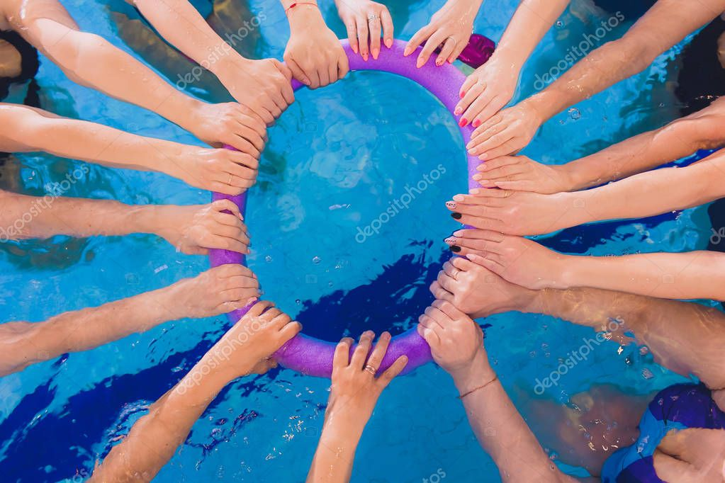 women trains in aqua aerobics, learn to swim. circle team hands