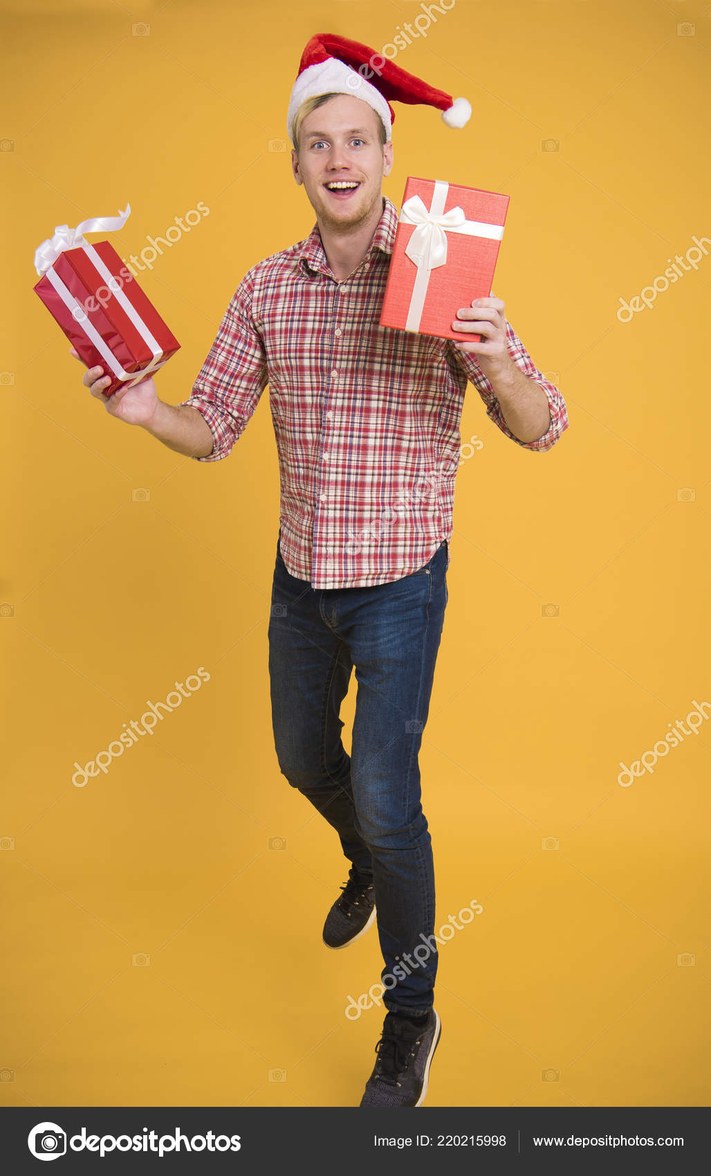 5b9d73a0e5389 Handsome man wear santa hat holding a lot of gift box on yellow background.  christmas and happy new year concept.