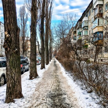 City street in winter. Vintage urban landscape in the winter. Parked cars, snow, blue sky with clouds