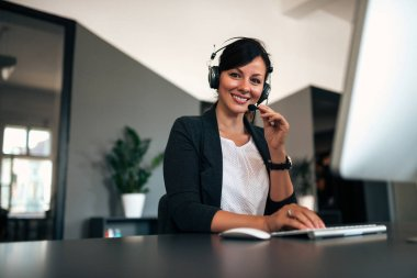 Portrait of happy female customer support operator at workplace.