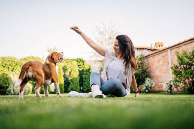 Lovely young woman playing with her beagle dog in the backyard.