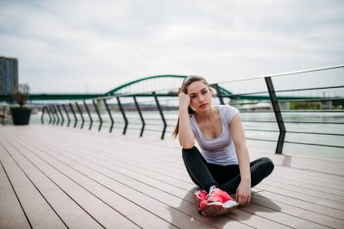 Portrait of a beautiful fit girl sitting on the floor at the city quay. Looking at camera.