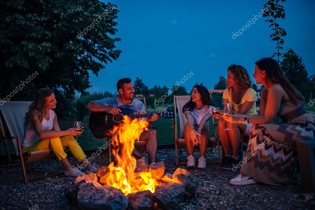Friends playing music and enjoying bonfire in nature.