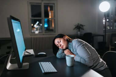 Tired young woman fall asleep while working overtime.
