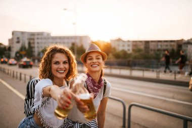 Cheers! Portrait of a two beautiful festival party girls having fun in the city.
