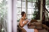 Nádherná žena čte knihu v zahradní sunroom nebo konzervatoře