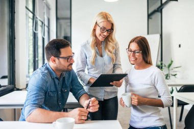 Three coworkers brainstorming during work process in modern office.