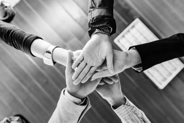 Unity and teamwork. Business people putting hands together.