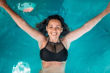 Top view of attractive young woman with authentic smile in the swimming pool.