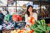 Gyönyörű fiatal nő vásárol zöldségek.