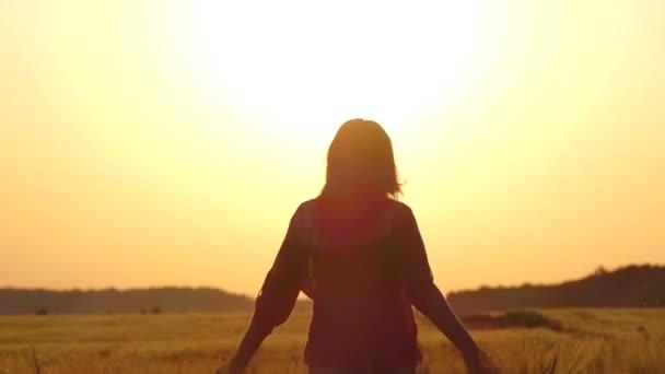 A girl runs across the field at sunset.