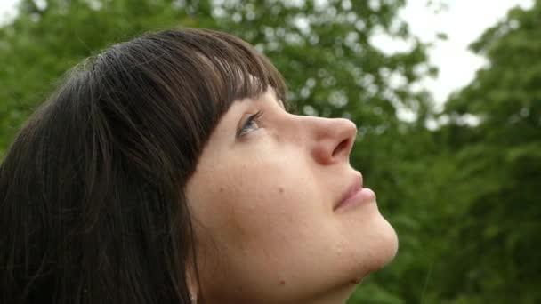ein schönes Mädchen blickt zu den fallenden Regentropfen und Wolken auf. Porträt eines Mädchens in der Natur aus nächster Nähe. Minuten des Glücks. Zeitlupe.