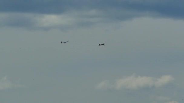 Das Flugzeug schleppt ein Segelflugzeug in den Himmel. Ein sportliches kleines Flugzeug mit Propeller fliegt zwischen den Wolken.