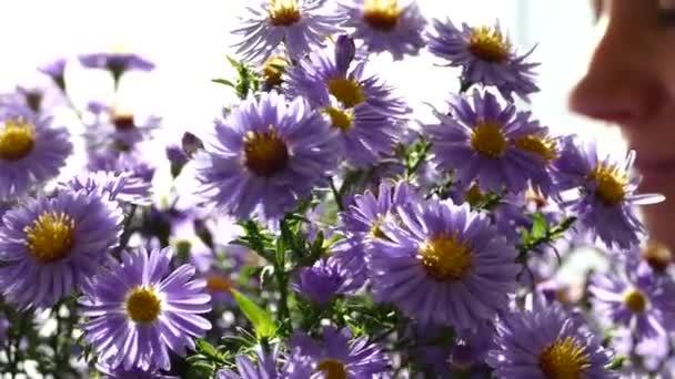 Dívka se raduje a sniffs květiny. Kytice z pole modré krásné květiny jako dárek.