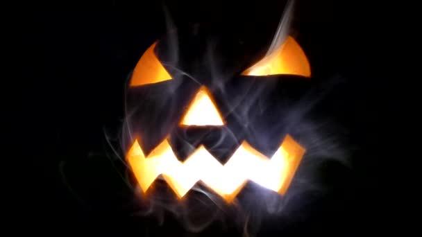 Halloween tök fényes fejét a reggel, és égő gyertyát. Halloween ünnepe. Félelmetes tök füst a fekete háttér.