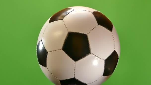 Fotbalový míč se točí na zeleném pozadí. Sportovní hry Soker. Liga mistrů. Mistrovství světa. Gól do brány.
