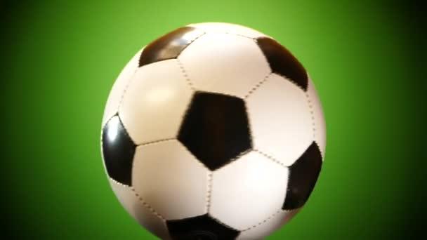 Fotbalový míč se točí na zeleném pozadí. Sportovní hry Soker. Liga mistrů. Mistrovství světa. Gól do brány