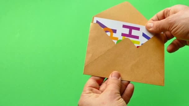 Happy Birthday. Get a birthday card in an envelope. Greeting card on a green background. Hold an envelope.