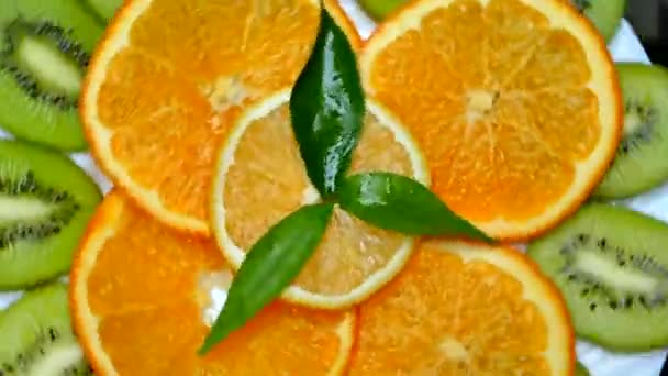Tropical fruits on a plate. Sliced kiwi orange lemon. Fruit close up on black background. Vitamins from nature.