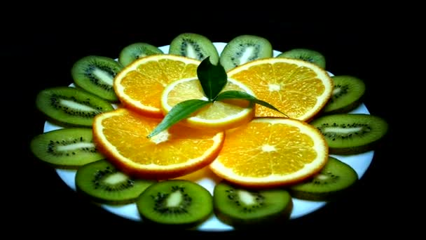 Tropical fruits on a plate. Sliced kiwi orange lemon. Fruit close up on black background. Vitamins from nature.