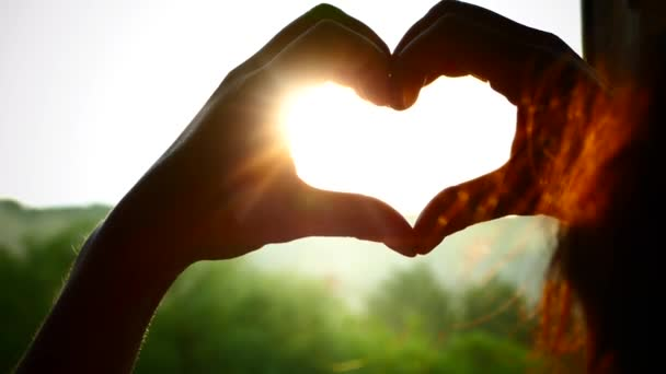 Kezek összehajtva. A nap sugarai napnyugtakor ragyognak át a szíven. A szerelem szimbóluma.