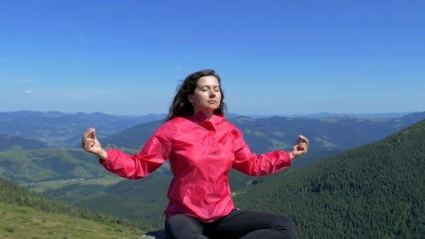 Dívka sedí na vrcholku hory a medituje. Klid v přírodě. Štěstí a klid