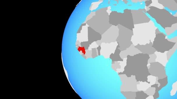 Guinea na modré politické globe. Obíhající kolem zeměkoule a přiblížení k zemi. 3D obrázek.