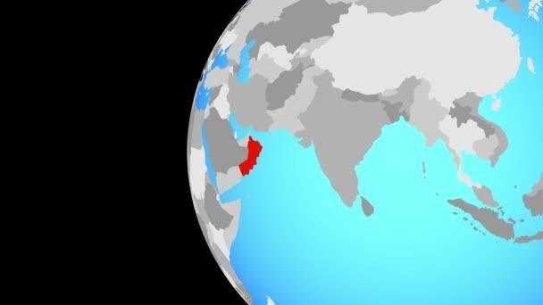 Omán na modré politické globe. Obíhající kolem zeměkoule a přiblížení k zemi. 3D obrázek
