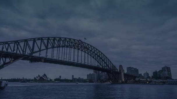 Holy grail timelapse of Sydney Harbour Bridge with the cityscape of Sydney skyscrapers and office buildings in the evening from daylight until darkness with the city illuminated by bright city lights.