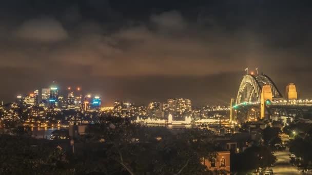 Velkolepé timelapse panoráma s Sydney Harbour Bridge v Sydney a osvětlené business centrum s mrakodrapy a kancelářské budovy.