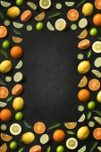 Flat lay assorted citrus fruits on black background. Text space image.