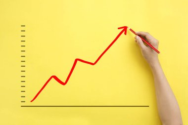 Hand drawing business growth chart upward.