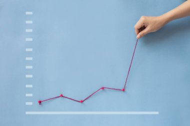 Conceptual hand pulling business finance growth chart line upwards on blue background.
