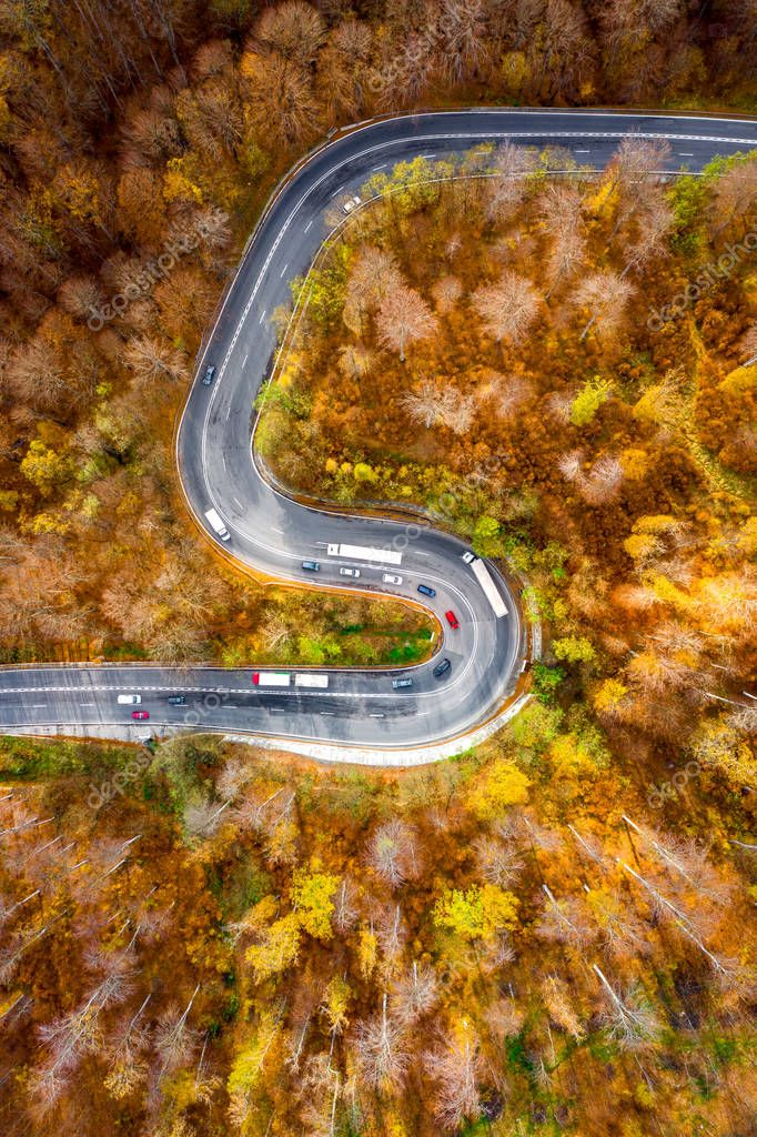 Winding curved road with cars and trucks on the road. Aerial view.
