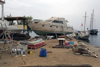 Fishing boats, wooden boats and ships on the lift in a shipyard in Bodrum, Turkey