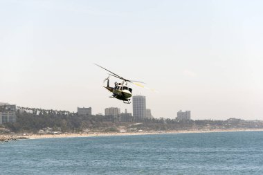 A view of a flying fire helicopter over the Malibu beach in summer time in California