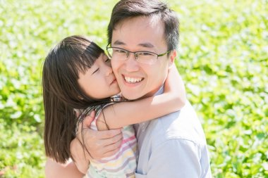 father and daughter smiling  happily in the park