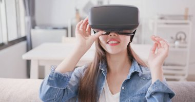 woman sitting  on sofa and wearing  virtual reality headset happily