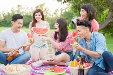 people eat watermelon happily and enjoy go on a picnic