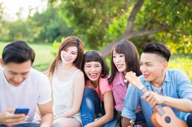 people using  phone happily and enjoying  picnic