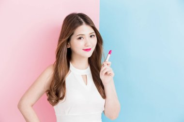 A beautiful girl that she is holding red lipstick isolated on a pink and blue background.
